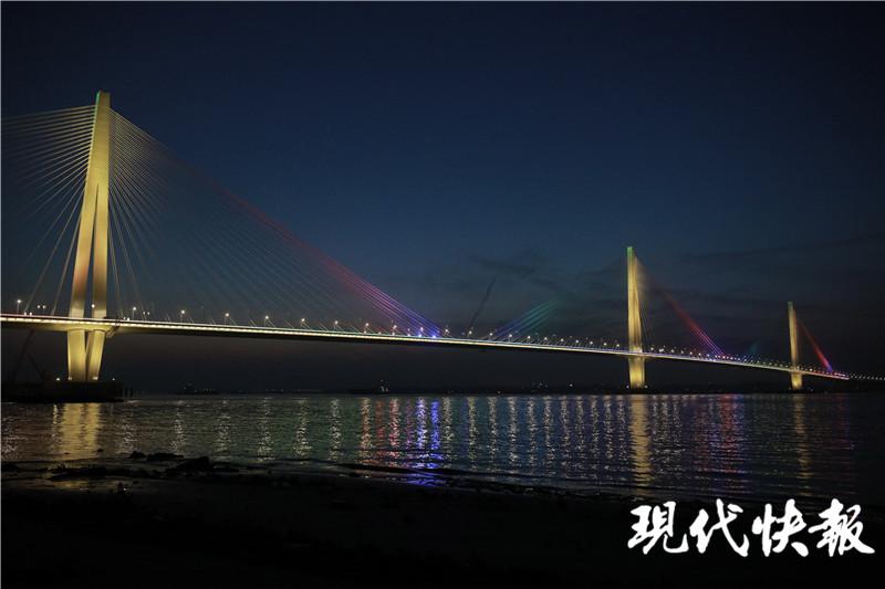 江心洲长江大桥的灯光准点亮起,进行亮灯调试,流光溢彩的索塔与桥面交相辉映,如彩色的长龙横卧江面,与城市夜景融为一体,曼妙无比。